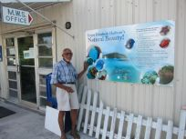 Basil Minns with a sign at Minns Water Sports.